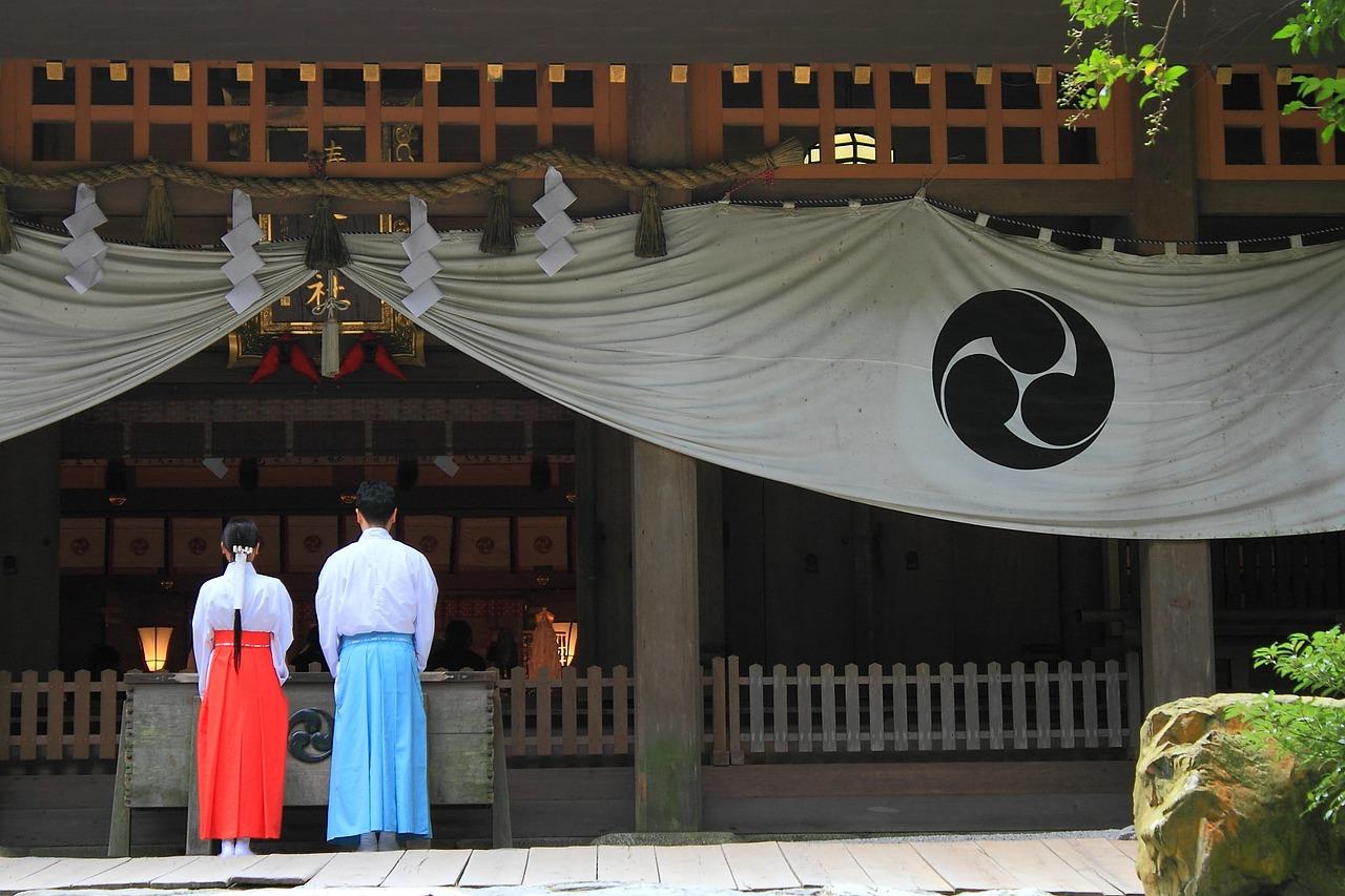 神社でお祈りするカップル