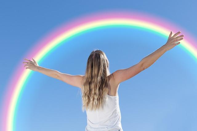 虹と手を広げる女性