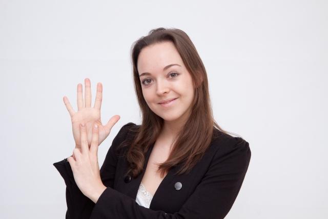 7つの指サインを出す外国人女性