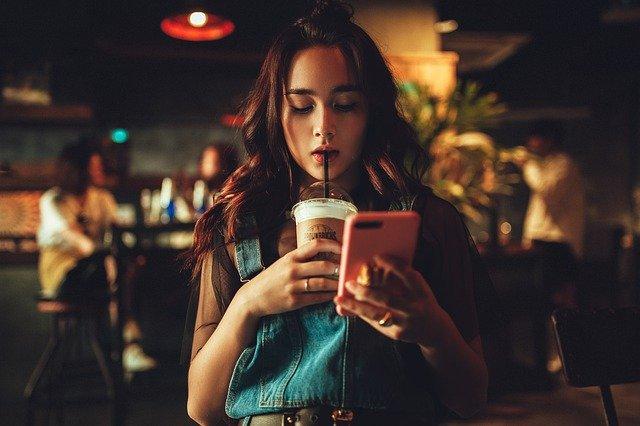 ジュースを飲みながら携帯を見ている女性